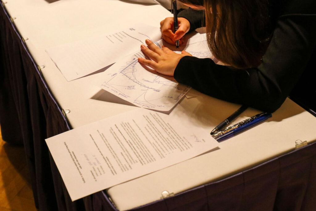 Egy asztalon papír lapok vannak, amikre egy lány kék tollal dolgozatát írja.