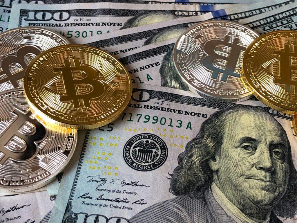 A képen több 100 dolláros bankjegy és kripto valuták fizikai formája látható.